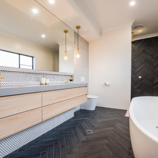 This is an example of a contemporary master bathroom in Sydney with engineered quartz benchtops, flat-panel cabinets, light wood cabinets, a freestanding tub, a one-piece toilet, white tile, mosaic tile, white walls, a wall-mount sink, black floor, an open shower and grey benchtops.