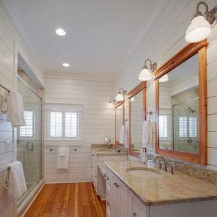 Großes Maritimes Badezimmer En Suite mit Unterbauwaschbecken, Lamellenschränken, weißen Schränken, Granit-Waschbecken/Waschtisch, Eckdusche, Toilette mit Aufsatzspülkasten, weißer Wandfarbe, braunem Holzboden, weißen Fliesen und Metrofliesen in Charleston