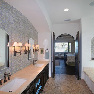 Example of a large tuscan master blue tile and cement tile brick floor drop-in bathtub design in Tampa with an undermount sink, furniture-like cabinets, dark wood cabinets, marble countertops and white walls