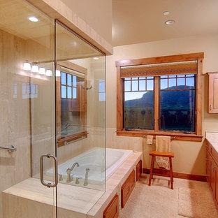 Ejemplo de cuarto de baño rústico, grande, con armarios con rebordes decorativos, puertas de armario naranjas, jacuzzi, ducha a ras de suelo, baldosas y/o azulejos de piedra, paredes beige y encimera de granito