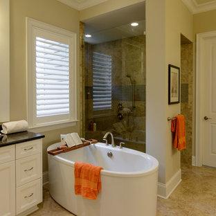 Diseño de cuarto de baño principal, actual, de tamaño medio, con armarios con paneles empotrados, puertas de armario blancas, bañera japonesa, ducha esquinera, baldosas y/o azulejos beige, paredes amarillas y ducha con puerta con bisagras