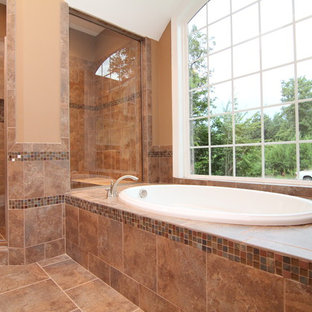 Inspiration for a large timeless master brown tile and ceramic tile ceramic tile bathroom remodel in Raleigh with an undermount sink, recessed-panel cabinets, medium tone wood cabinets, granite countertops, a one-piece toilet and beige walls