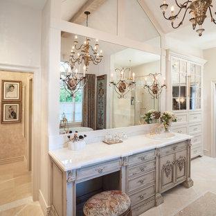 Стильный дизайн: большая главная ванная комната в классическом стиле с накладной раковиной, фасадами островного типа, бежевыми фасадами, отдельно стоящей ванной, угловым душем, бежевой плиткой, каменной плиткой, мраморной столешницей, белыми стенами, мраморным полом, унитазом, тумбой под одну раковину и балками на потолке - последний тренд