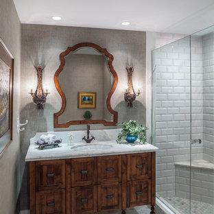 Foto på ett stort vit badrum med dusch, med ett undermonterad handfat, möbel-liknande, skåp i mellenmörkt trä, marmorbänkskiva, en dusch i en alkov, en toalettstol med hel cisternkåpa, vit kakel, tunnelbanekakel, beige väggar, marmorgolv, grått golv och dusch med skjutdörr