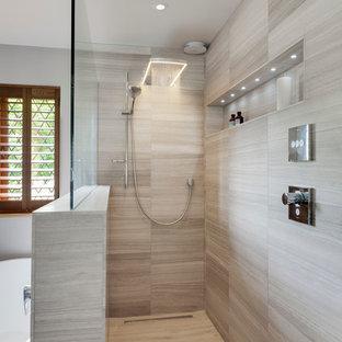 Modern inredning av ett stort en-suite badrum, med släta luckor, skåp i ljust trä, ett fristående badkar, en öppen dusch, grå kakel, stenhäll, grå väggar, kalkstensgolv och marmorbänkskiva