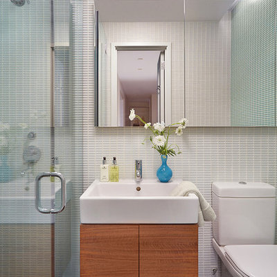 Alcove shower - mid-sized contemporary 3/4 ceramic tile and black floor alcove shower idea in New York with flat-panel cabinets, medium tone wood cabinets, a two-piece toilet, a wall-mount sink and a hinged shower door