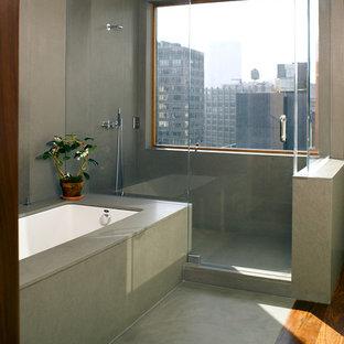 Idées déco pour une douche en alcôve moderne avec une baignoire encastrée et béton au sol.