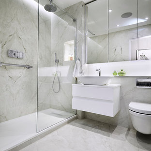 This is an example of a medium sized modern ensuite bathroom in London with glass-front cabinets, a walk-in shower, a wall mounted toilet, grey tiles, marble tiles, marble flooring, a wall-mounted sink, quartz worktops and a hinged door.