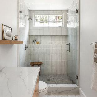 Diseño de cuarto de baño de estilo de casa de campo, de tamaño medio, con armarios con paneles lisos, puertas de armario de madera clara, baldosas y/o azulejos blancos, baldosas y/o azulejos de terracota, lavabo bajoencimera, encimera de cuarzo compacto, ducha con puerta con bisagras, encimeras blancas, ducha empotrada, paredes grises y suelo blanco