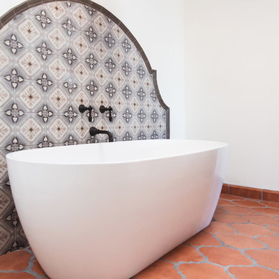 Huge southwest master multicolored tile and ceramic tile terra-cotta tile and orange floor bathroom photo in San Diego with raised-panel cabinets, medium tone wood cabinets, white walls, a vessel sink, a hinged shower door and gray countertops