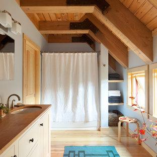 Inspiration för lantliga beige en-suite badrum, med beige skåp, en dusch i en alkov, blå väggar, mellanmörkt trägolv, ett undermonterad handfat, träbänkskiva, beiget golv och dusch med duschdraperi
