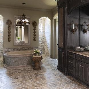Diseño de cuarto de baño principal, tradicional, grande, con armarios con paneles con relieve, puertas de armario de madera oscura, bañera exenta, ducha abierta, ducha abierta y suelo de ladrillo