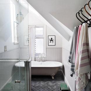 Inredning av ett klassiskt badrum med dusch, med ett badkar med tassar, vita väggar, grått golv och dusch med gångjärnsdörr