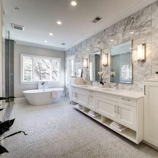 На фото: огромная главная ванная комната в стиле современная классика с фасадами в стиле шейкер, белыми фасадами, отдельно стоящей ванной, душем в нише, серой плиткой, керамогранитной плиткой, серыми стенами, врезной раковиной, серым полом, душем с распашными дверями и белой столешницей с
