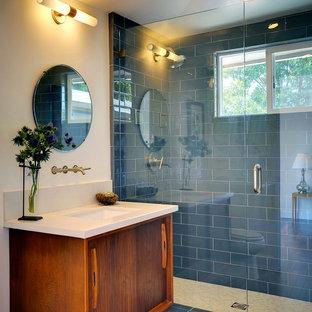 Immagine di una stanza da bagno moderna con consolle stile comò, piastrelle blu, piastrelle di vetro, lavabo sottopiano, ante in legno scuro e doccia alcova