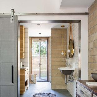 Modelo de cuarto de baño principal y ladrillo, de estilo de casa de campo, ladrillo, con ladrillo, baldosas y/o azulejos beige, paredes blancas, suelo de cemento, lavabo suspendido y suelo gris