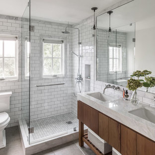 На фото: главная ванная комната в стиле кантри с плоскими фасадами, темными деревянными фасадами, угловым душем, раздельным унитазом, белой плиткой, плиткой кабанчик, белыми стенами, врезной раковиной, серым полом, душем с распашными дверями и белой столешницей с