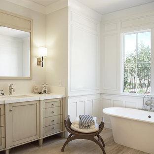 フェニックスの広いトランジショナルスタイルのおしゃれなマスターバスルーム (置き型浴槽、白い壁、アンダーカウンター洗面器、落し込みパネル扉のキャビネット、ベージュのキャビネット、アルコーブ型シャワー、白いタイル、サブウェイタイル、ライムストーンの床、クオーツストーンの洗面台、ベージュの床、開き戸のシャワー、白い洗面カウンター、トイレ室、洗面台2つ、造り付け洗面台、板張り壁) の写真