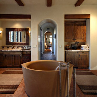 Large tuscan master ceramic tile terra-cotta floor japanese bathtub photo in Phoenix with shaker cabinets, dark wood cabinets, an undermount sink, granite countertops and beige walls