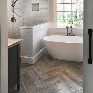 Idéer för mellanstora lantliga en-suite badrum, med skåp i shakerstil, grå skåp, ett fristående badkar, en hörndusch, en toalettstol med separat cisternkåpa, vit kakel, keramikplattor, grå väggar, klinkergolv i keramik, ett undermonterad handfat, marmorbänkskiva, grått golv och dusch med gångjärnsdörr