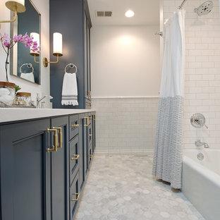 Diseño de cuarto de baño clásico renovado, de tamaño medio, con armarios tipo mueble, puertas de armario azules, bañera empotrada, ducha empotrada, sanitario de dos piezas, baldosas y/o azulejos blancos, baldosas y/o azulejos de cerámica, paredes blancas, suelo de mármol, lavabo bajoencimera, encimera de cuarzo compacto, suelo blanco y ducha con cortina
