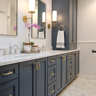 Medium sized classic family bathroom in Chicago with freestanding cabinets, blue cabinets, an alcove bath, an alcove shower, a two-piece toilet, white tiles, ceramic tiles, white walls, marble flooring, a submerged sink, engineered stone worktops, white floors and a shower curtain.