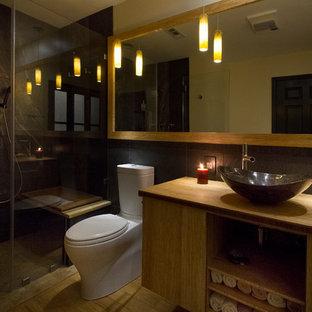 На фото: главная ванная комната среднего размера в современном стиле с настольной раковиной, светлыми деревянными фасадами, столешницей из дерева, душем без бортиков, раздельным унитазом, керамогранитной плиткой, желтыми стенами, полом из бамбука, плоскими фасадами, черной плиткой, желтой столешницей, желтым полом и душем с распашными дверями с