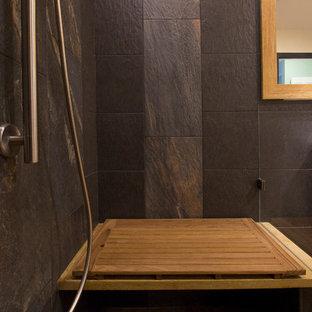 Cette image montre une salle de bain principale design de taille moyenne avec une vasque, un placard à porte plane, des portes de placard en bois clair, un plan de toilette en bois, une douche à l'italienne, un WC séparé, un carrelage noir, des carreaux de porcelaine, un mur jaune, un sol en bambou, un sol jaune, une cabine de douche à porte battante et un plan de toilette jaune.
