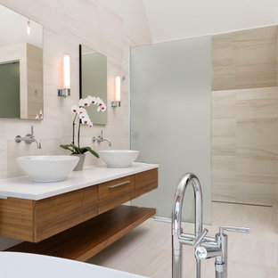 This is an example of a medium sized contemporary bathroom in Ottawa with a vessel sink, flat-panel cabinets, medium wood cabinets, engineered stone worktops, beige tiles, stone tiles, a freestanding bath, beige floors, an open shower and white worktops.