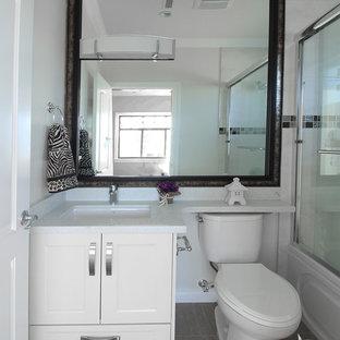 Esempio di una piccola stanza da bagno con doccia contemporanea con lavabo sottopiano, ante con riquadro incassato, ante bianche, top in quarzite, vasca ad alcova, vasca/doccia, WC monopezzo, piastrelle bianche, piastrelle di vetro, pareti beige e parquet chiaro
