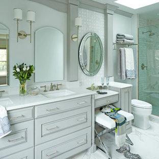 Ejemplo de cuarto de baño principal, clásico, de tamaño medio, con lavabo bajoencimera, armarios con paneles con relieve, puertas de armario grises, encimera de cuarzo compacto, ducha doble, baldosas y/o azulejos grises, baldosas y/o azulejos en mosaico, paredes grises y suelo de baldosas de porcelana