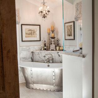 Diseño de cuarto de baño principal, bohemio, de tamaño medio, con bañera exenta, baldosas y/o azulejos de mármol y paredes blancas