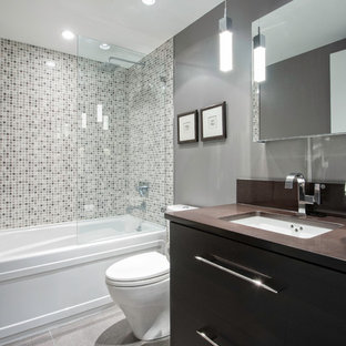 Small contemporary bathroom in Vancouver with mosaic tile, an undermount sink, flat-panel cabinets, dark wood cabinets, engineered quartz benchtops, an alcove tub, a shower/bathtub combo, a one-piece toilet, gray tile, grey walls and ceramic floors.