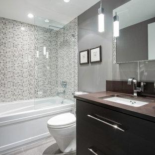 Idées déco pour une petit salle de bain contemporaine avec carrelage en mosaïque, un lavabo encastré, un placard à porte plane, des portes de placard en bois sombre, un plan de toilette en quartz modifié, une baignoire en alcôve, un combiné douche/baignoire, un WC à poser, un carrelage gris, un mur gris et un sol en carrelage de céramique.