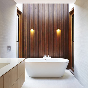 Design ideas for a large contemporary master bathroom in Melbourne with furniture-like cabinets, light wood cabinets, a freestanding tub, an alcove shower, white tile and an integrated sink.