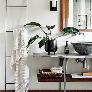 Design ideas for a contemporary bathroom in San Francisco with open cabinets, white walls, a vessel sink, stainless steel benchtops, white floor and grey benchtops.