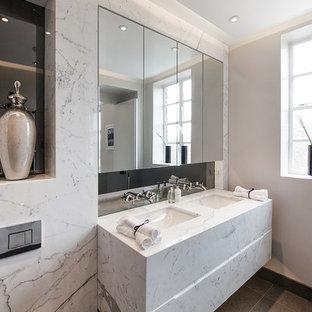 Ejemplo de cuarto de baño principal, retro, pequeño, con armarios con paneles lisos, puertas de armario blancas, ducha abierta, sanitario de una pieza, baldosas y/o azulejos grises, baldosas y/o azulejos con efecto espejo, paredes grises, suelo de mármol, lavabo bajoencimera y encimera de mármol