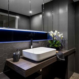 Mittelgroßes Modernes Badezimmer mit verzierten Schränken, Schränken im Used-Look, bodengleicher Dusche, Wandtoilette, braunen Fliesen, Porzellanfliesen, brauner Wandfarbe, Keramikboden, Aufsatzwaschbecken und Laminat-Waschtisch in Brisbane