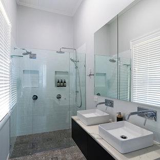 ブリスベンの中サイズのモダンスタイルのおしゃれなマスターバスルーム (家具調キャビネット、濃色木目調キャビネット、洗い場付きシャワー、サブウェイタイル、グレーの壁、テラゾーの床、コンソール型シンク、珪岩の洗面台、マルチカラーの床、白い洗面カウンター) の写真