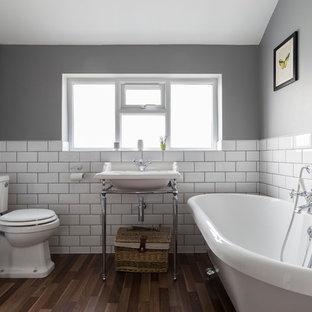Inredning av ett industriellt badrum, med ett badkar med tassar, en toalettstol med separat cisternkåpa, vit kakel, tunnelbanekakel, grå väggar, ett konsol handfat och mörkt trägolv