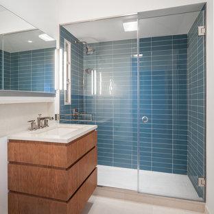 Ispirazione per una stanza da bagno padronale moderna di medie dimensioni con lavabo sottopiano, ante lisce, ante in legno scuro, top in quarzo composito, doccia alcova, piastrelle blu, piastrelle di vetro, pareti bianche e pavimento in pietra calcarea