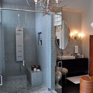 Modelo de cuarto de baño principal, moderno, extra grande, con armarios tipo mueble, puertas de armario de madera en tonos medios, encimera de madera, ducha a ras de suelo, baldosas y/o azulejos azules, suelo de baldosas tipo guijarro, paredes azules y suelo de baldosas tipo guijarro
