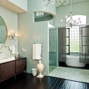 Foto di un'ampia stanza da bagno padronale design con consolle stile comò, ante in legno bruno, vasca freestanding, doccia doppia, piastrelle verdi, piastrelle di vetro, pareti verdi, parquet scuro, lavabo a bacinella e top in legno