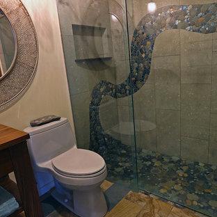 Esempio di una stanza da bagno con doccia american style di medie dimensioni con consolle stile comò, ante in legno bruno, doccia alcova, WC monopezzo, piastrelle nere, piastrelle grigie, piastrelle di ciottoli, pareti beige, lavabo a bacinella e top in legno