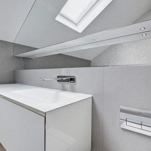 Ispirazione per una stanza da bagno per bambini contemporanea di medie dimensioni con ante lisce, ante bianche, vasca freestanding, piastrelle grigie, piastrelle in ceramica, pavimento in cementine, top in vetro e pavimento grigio