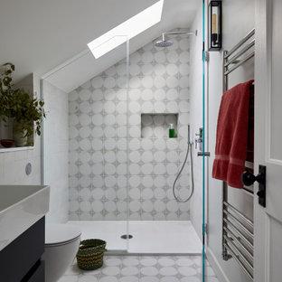 Inredning av ett modernt vit vitt badrum för barn, med släta luckor, en vägghängd toalettstol, flerfärgad kakel, keramikplattor, vita väggar, klinkergolv i keramik, bänkskiva i akrylsten, flerfärgat golv, dusch med gångjärnsdörr, svarta skåp, en dusch i en alkov och ett konsol handfat