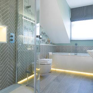 Cette image montre une salle de bain design de taille moyenne avec un WC suspendu, un carrelage gris, un sol gris, une baignoire posée, une douche d'angle et des carreaux de céramique.