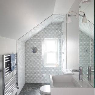 Inredning av ett klassiskt stort vit vitt badrum för barn, med med dusch som är öppen, ett konsol handfat, släta luckor, skåp i mörkt trä, ett fristående badkar, våtrum, en vägghängd toalettstol, grå kakel, stenhäll, grå väggar, skiffergolv, bänkskiva i kvartsit och grått golv