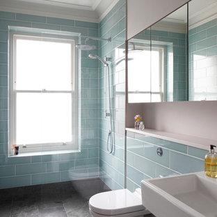 ロンドンの広いトランジショナルスタイルのおしゃれな子供用バスルーム (壁掛け式トイレ、オープンシャワー、フラットパネル扉のキャビネット、濃色木目調キャビネット、置き型浴槽、洗い場付きシャワー、グレーのタイル、石スラブタイル、グレーの壁、スレートの床、コンソール型シンク、珪岩の洗面台、グレーの床、白い洗面カウンター、トイレ室、洗面台2つ、造り付け洗面台、格子天井) の写真