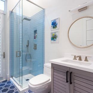 Idee per una stanza da bagno con doccia al mare di medie dimensioni con ante a persiana, ante grigie, doccia ad angolo, piastrelle blu, pareti bianche, lavabo sottopiano, WC a due pezzi, pavimento in gres porcellanato, top in superficie solida e porta doccia a battente